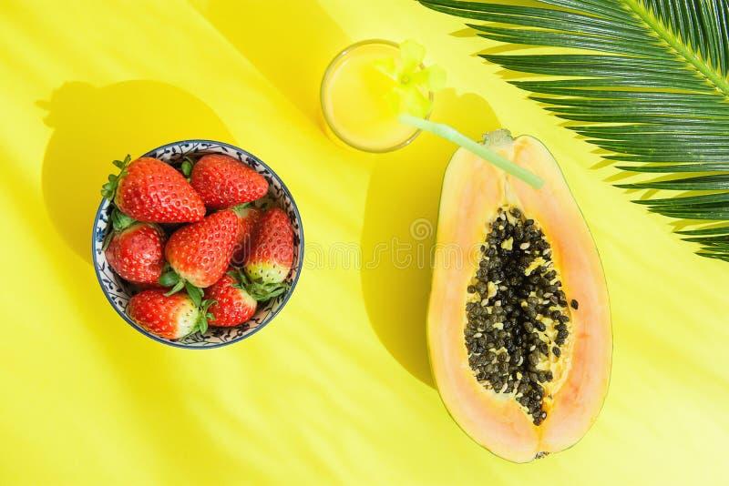 在碗菠萝汁的被对分的成熟番木瓜新鲜的草莓在与秸杆棕榈叶的高玻璃在黄色背景 库存照片