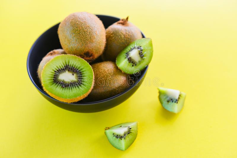 在碗-在桌上的新鲜的猕猴桃的猕猴桃切片有黄色背景 免版税图库摄影