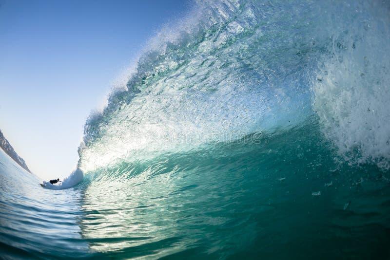在碰撞的水游泳后的波浪冲浪者 库存图片