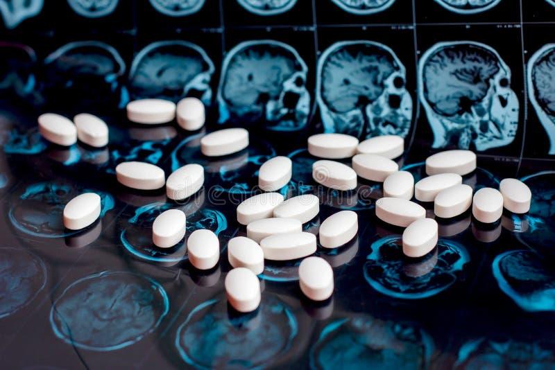 在磁性脑子共鸣扫描mri背景的白色配药医学药片 药房题材,医疗保健 免版税库存图片