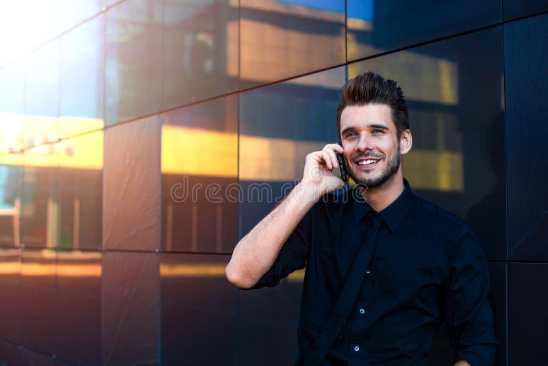在礼服穿戴的愉快的微笑的商人谈话与伙伴通过手机 图库摄影