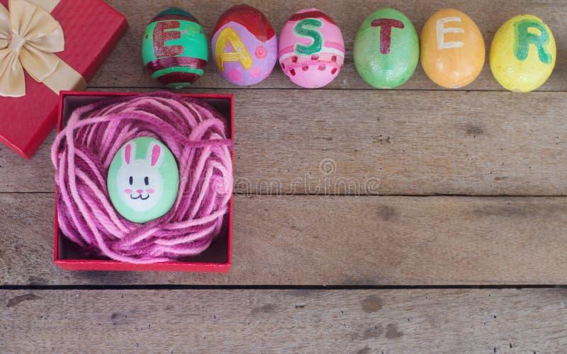 在礼物盒的复活节彩蛋在木 免版税库存图片