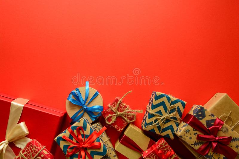 在礼物纸包裹的圣诞节礼物的顶视图装饰用在红色纸背景的丝带 库存照片
