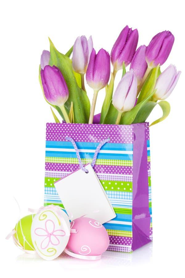 在礼物袋子和复活节彩蛋的紫色郁金香花束 库存图片