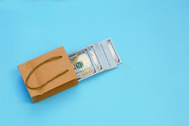 在礼物袋子的很多100美金在与拷贝空间的蓝色背景 现金礼品 当前的商业 背景袋子概念行程购物的白人妇女 库存照片
