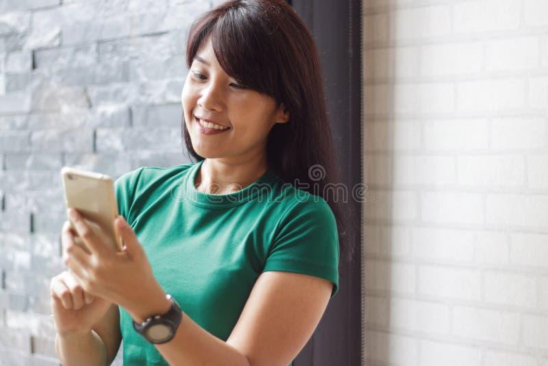 在社会网络的年轻女性举行的智能手机和读内容 复制空间,选择聚焦 库存图片