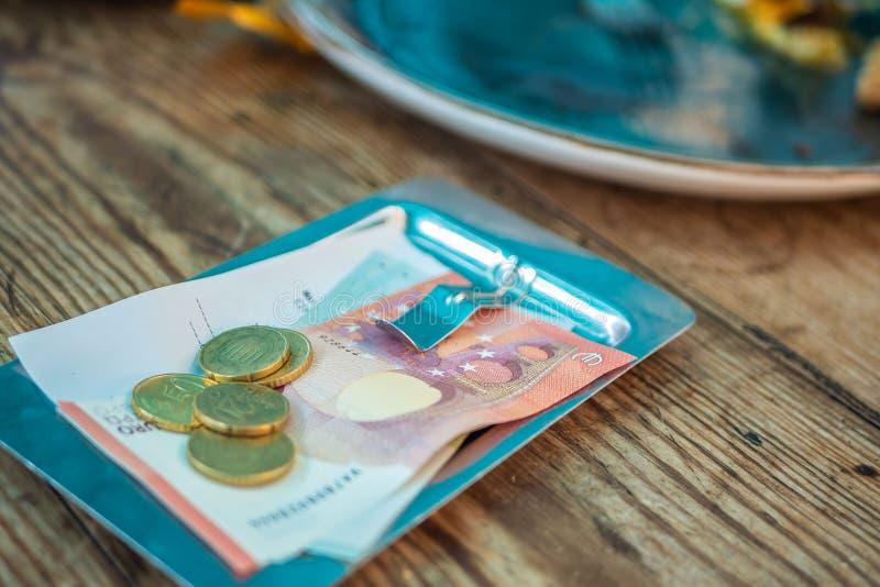 在票据的付款在一块板材的一个咖啡馆在一张木桌上 免版税库存图片