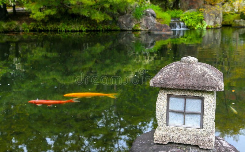 在禅宗的红色和黄色鲤鱼鱼在有灯笼的日本筑成池塘 图库摄影