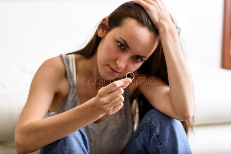 在离婚以后被压下的恼怒和被触犯的妻子,拿着用手婚戒坐室地板 图库摄影
