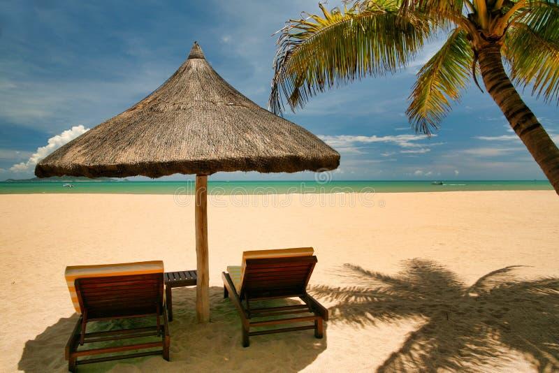 在离开的海滩的两个空的太阳懒人海南岛 图库摄影