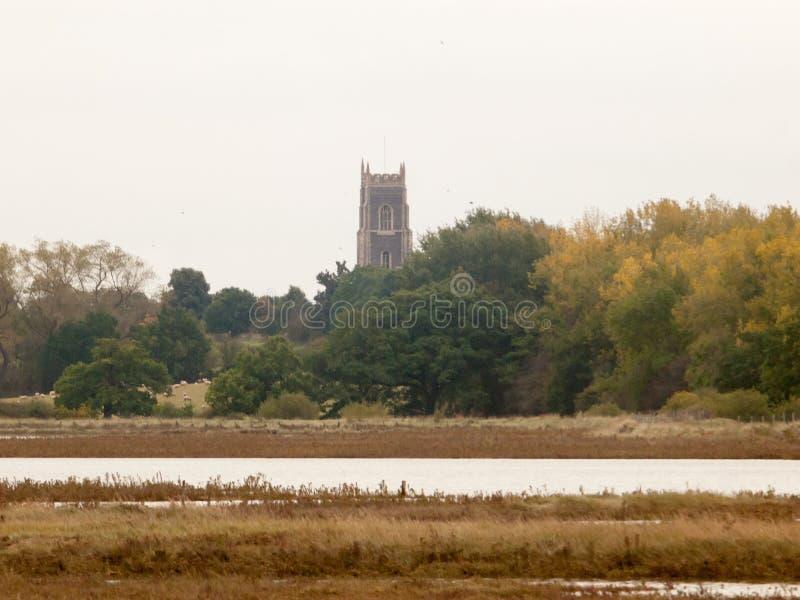 在离教会上面尖顶阴云密布河海岸的附近 库存图片