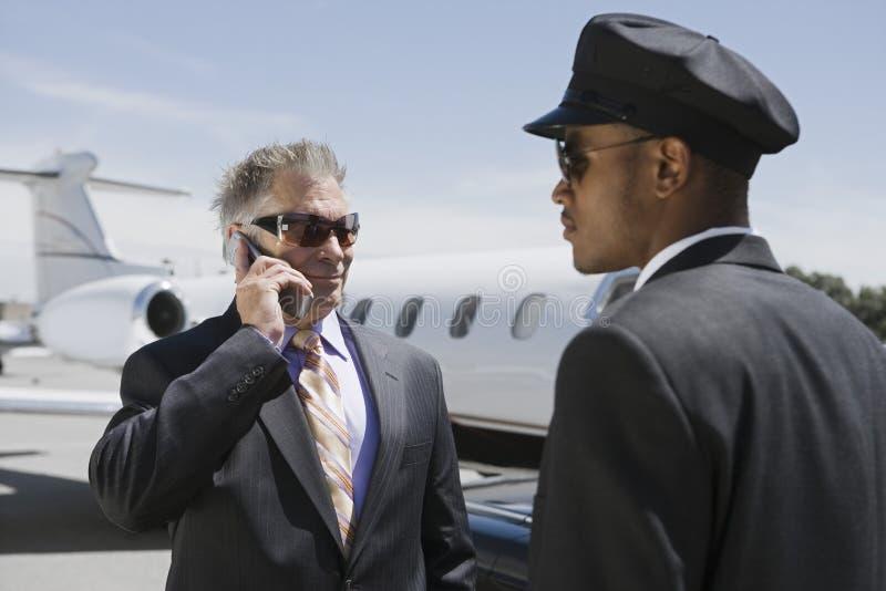 在私人喷气式飞机之外的资深商人在汽车夫的电话 免版税库存图片