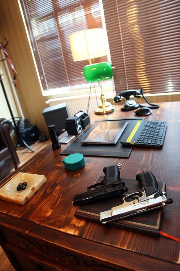 在私家侦探的书桌上的两杆枪 库存照片