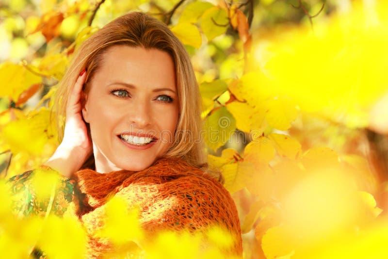 在秋叶前面的可爱的中年妇女 免版税图库摄影