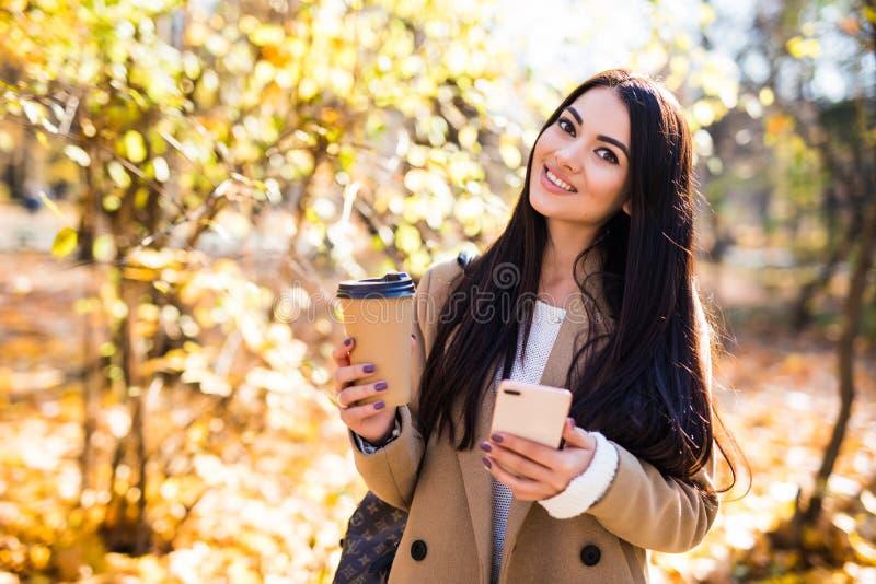 在秋天外套打扮的美丽的年轻女人户外,喝咖啡,使用手机 免版税库存图片