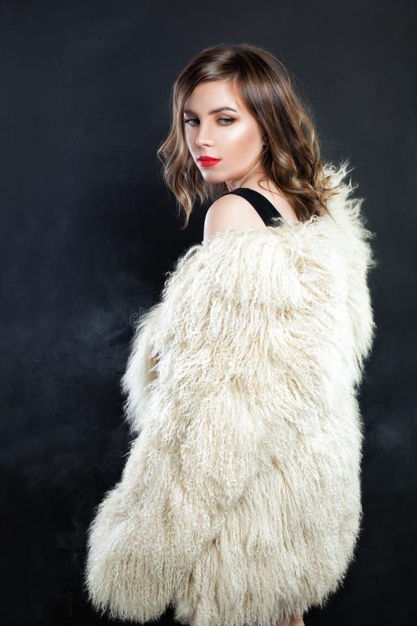 在秋天或冬天皮大衣的逗人喜爱的妇女时装模特儿 免版税库存照片