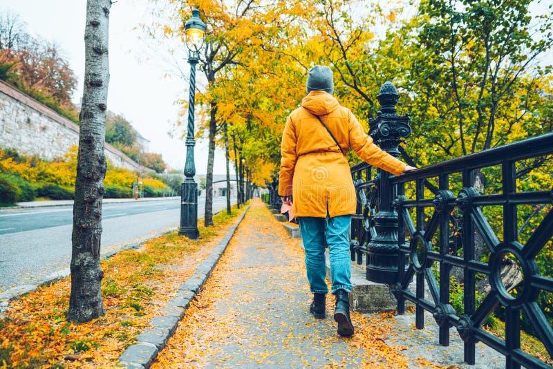 在秋天期间,走在街道上的妇女黄色充分离开 图库摄影