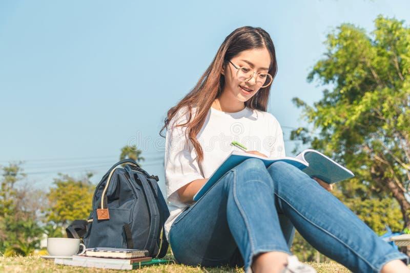 在秋天森林里读书的美女盖用一条温暖的毯子 妇女在一棵树附近坐在夏天森林和举行里 免版税库存图片