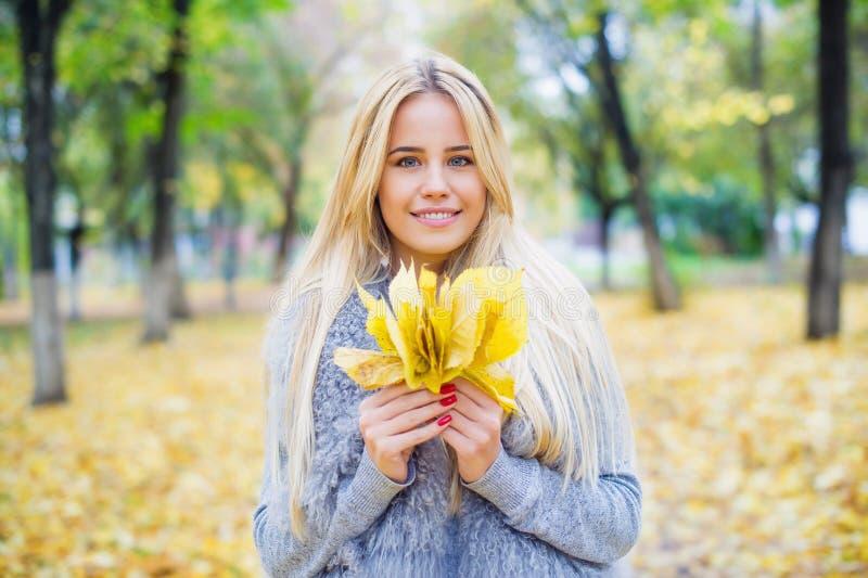 在秋天背景的美丽的妇女画象 免版税图库摄影