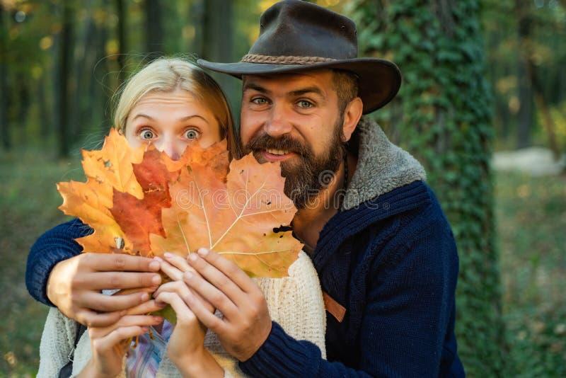 在秋天自然背景的秋天夫妇 有英俊的有胡子的人的无忧无虑的年轻女人时髦葡萄酒套头衫的或 图库摄影