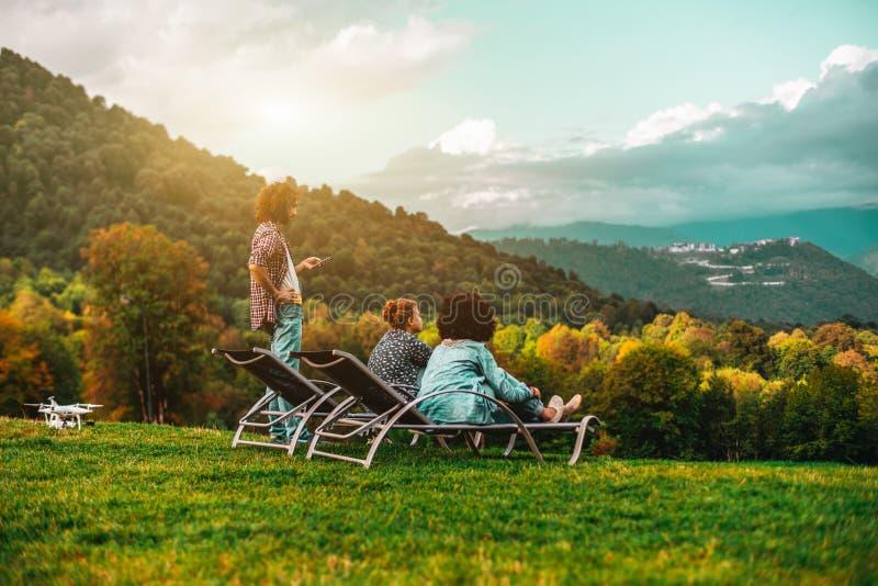 在秋天草甸享受风景的朋友 免版税库存照片