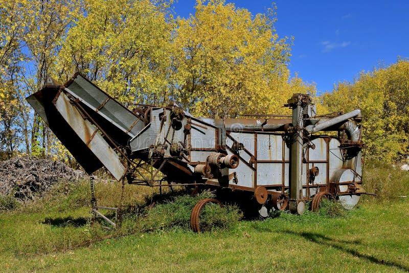 在秋天转动的叶子的老打谷机 免版税库存照片