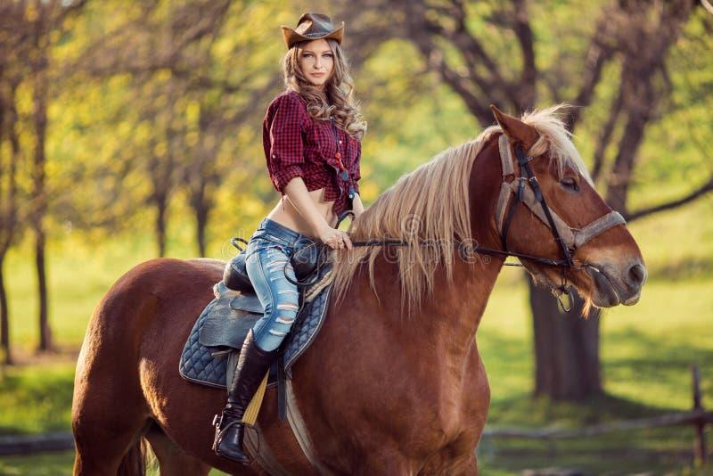 在秋天领域的美丽的女孩骑乘马 免版税库存照片