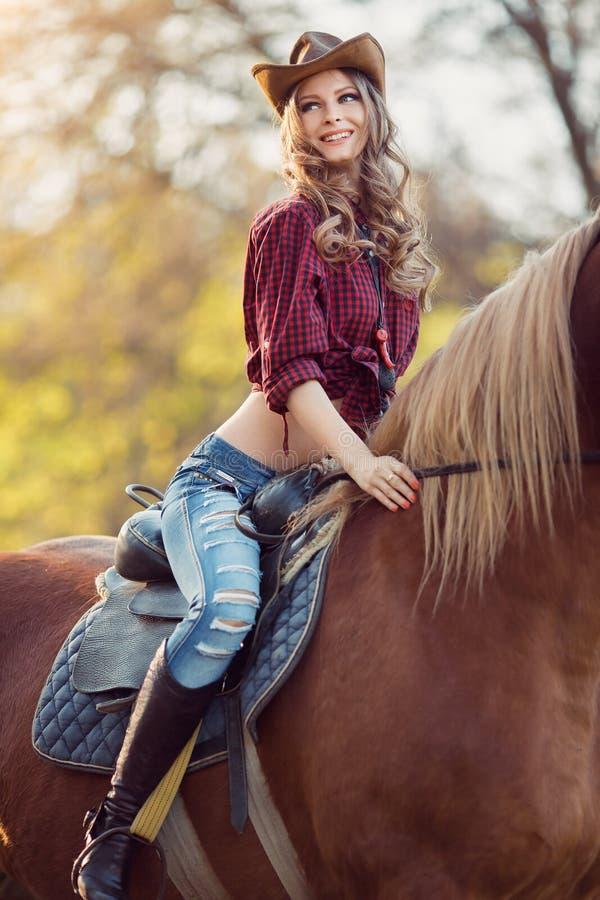 在秋天领域的美丽的微笑的女孩骑乘马 免版税库存图片