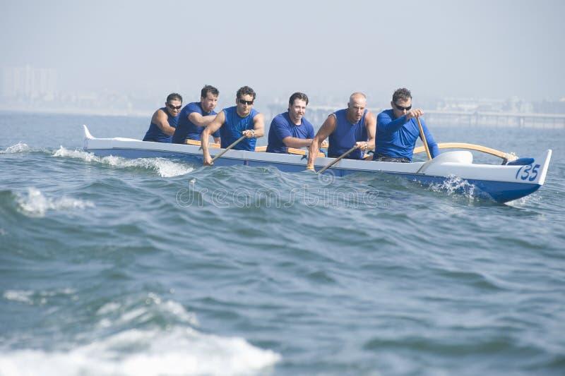 在种族的舷外架乘独木舟的队 库存图片