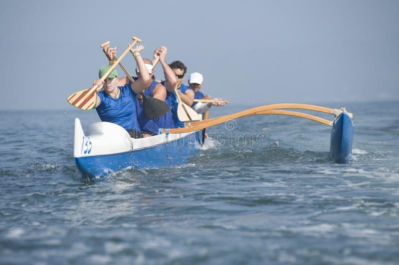 在种族的舷外架乘独木舟的队 免版税库存图片