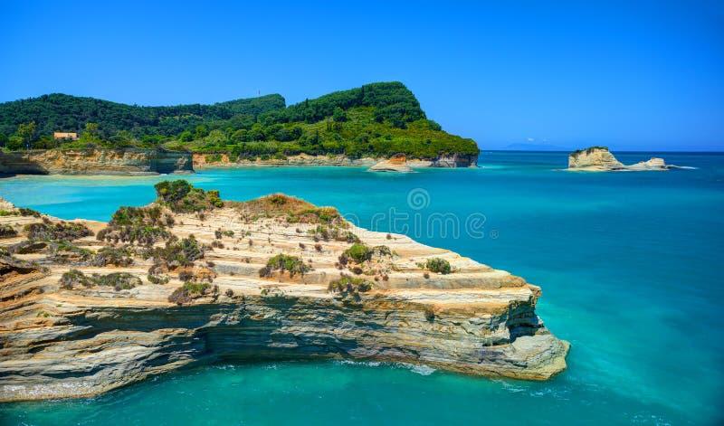 在科孚岛海岛青山山和沙子讨嫌的岩石和游泳人民的美丽的景色在爱奥尼亚人蓝色海 沙子小山ro 免版税图库摄影