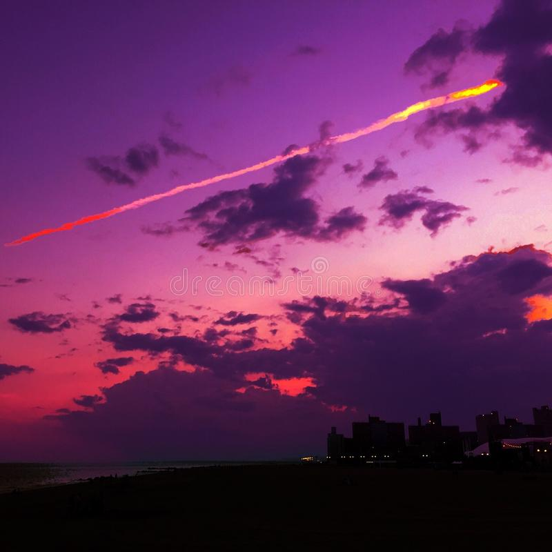 在科尼岛海滩的紫色日落 免版税库存照片