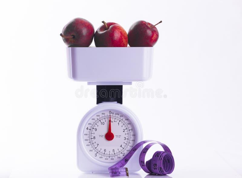 在秤的三个红色苹果与卷尺 免版税库存图片