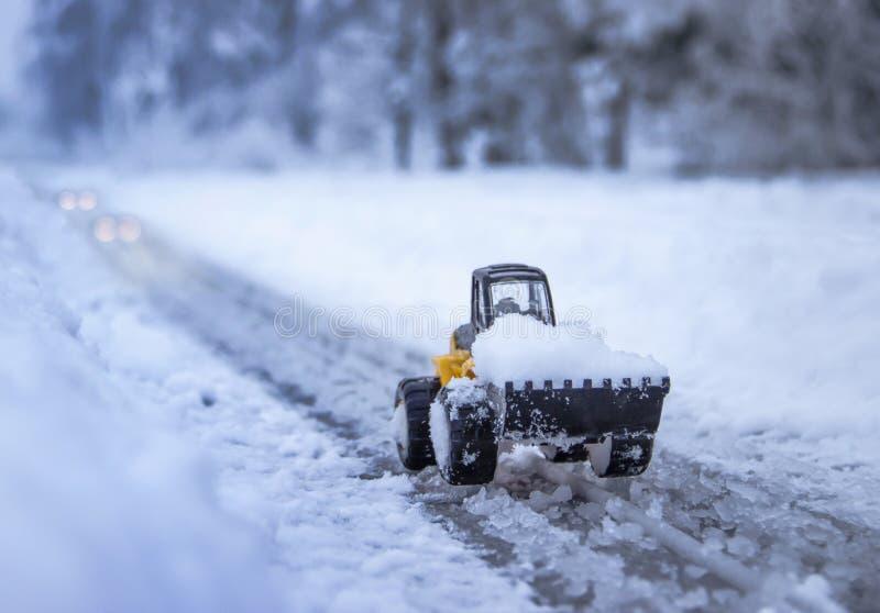 在积雪的公路牵引车上清除在距离的雪暮色车灯光 库存照片