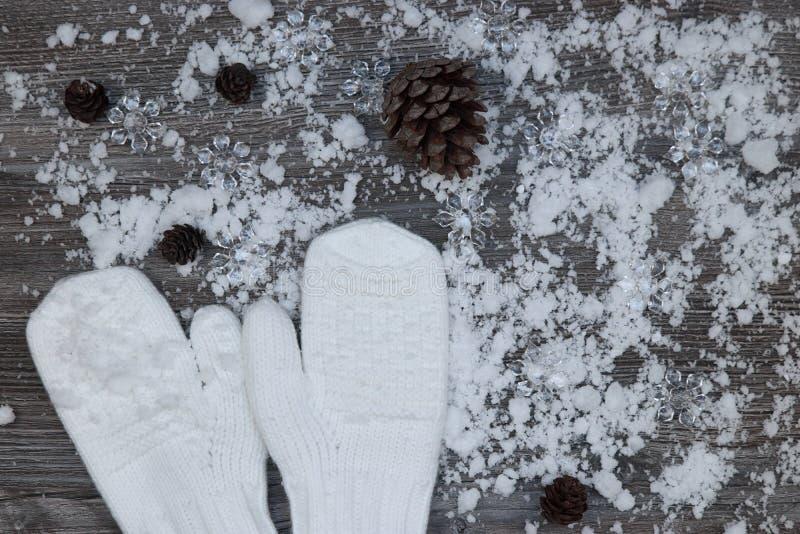 在积雪的木表面wi背景的白色手套  免版税库存图片