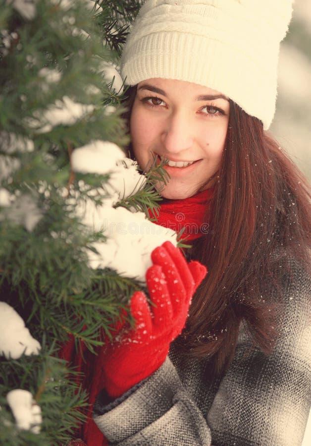 在积雪的杉木后的年轻美丽的妇女 免版税图库摄影