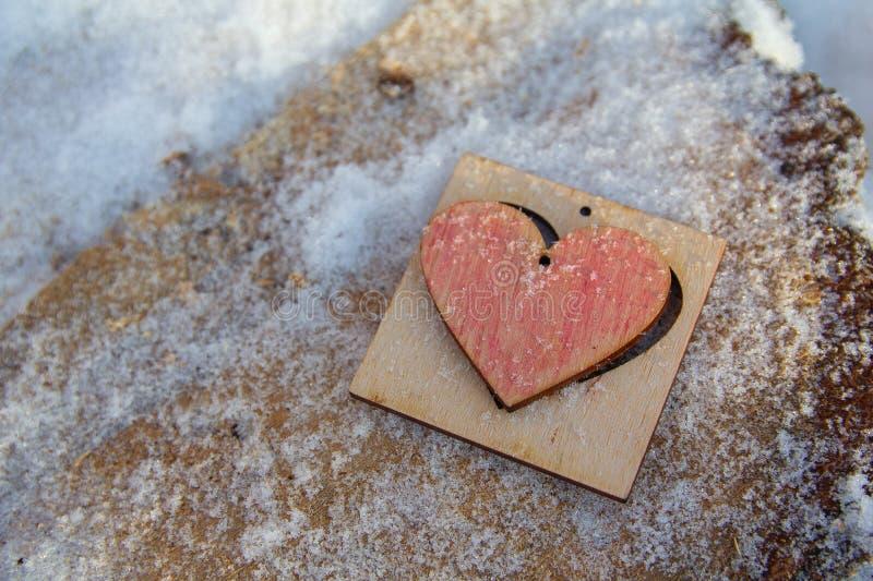 在积雪的表面后的木心脏 免版税库存照片