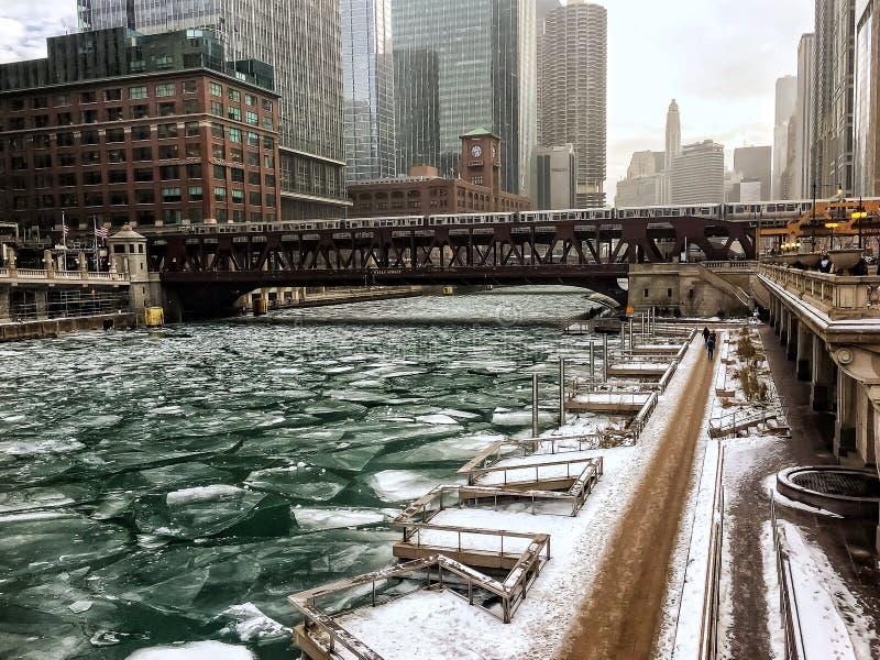 在积雪的riverwalk的脚印沿着在大雪期间的芝加哥河在12月下午 免版税库存图片