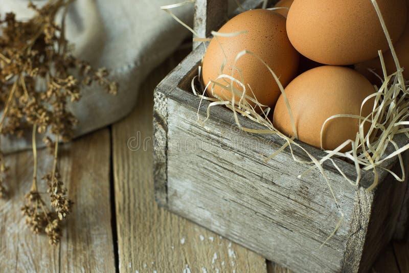 在秸杆的布朗有机鸡蛋在板条厨房用桌亚麻布餐巾的葡萄酒木箱烘干花 在土气的复活节构成 免版税库存图片