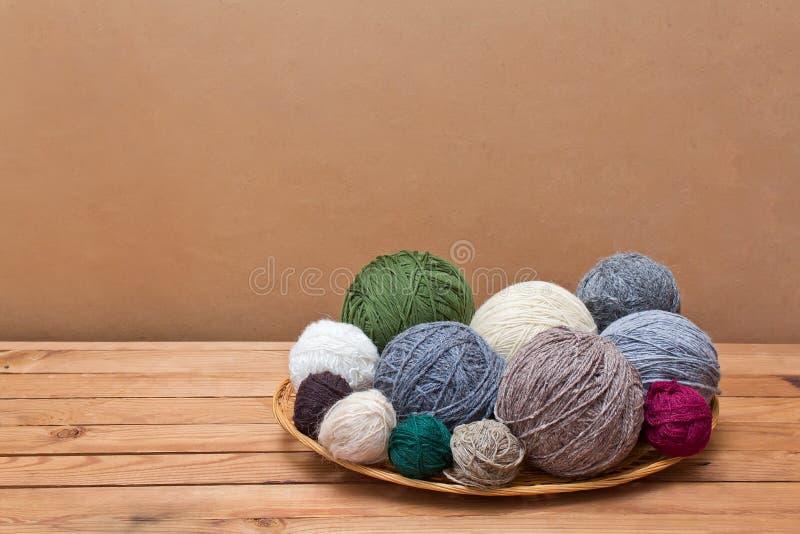 在秸杆篮子的多彩多姿的毛线球在一张木桌上 免版税库存图片