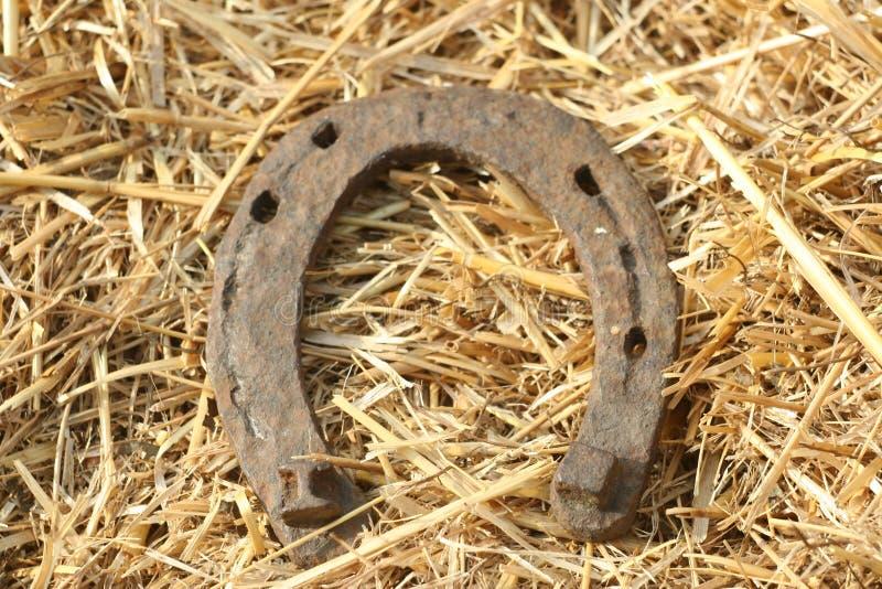 在秸杆背景-在乡村模式的土气场面的生锈的马掌 老铁马掌-好运井标志和吉祥人  库存照片