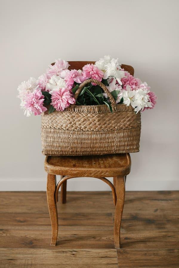 在秸杆袋子的时髦的桃红色和白色牡丹在木土气椅子在屋子里 国际妇女` s天 日愉快的母亲 你好 免版税库存照片