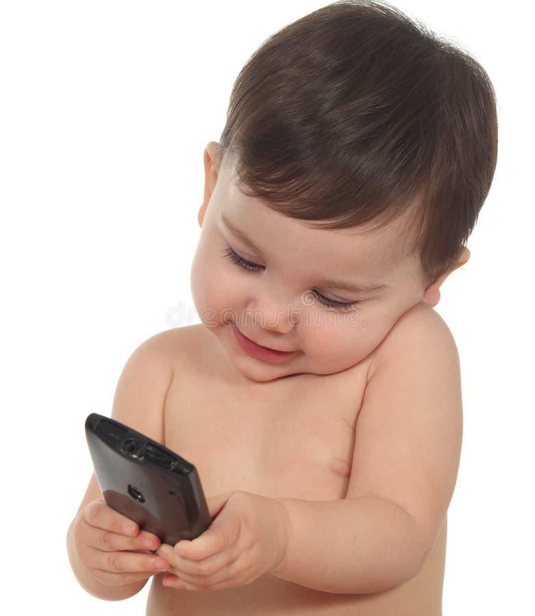 在移动电话愉快和集中的婴孩 免版税图库摄影