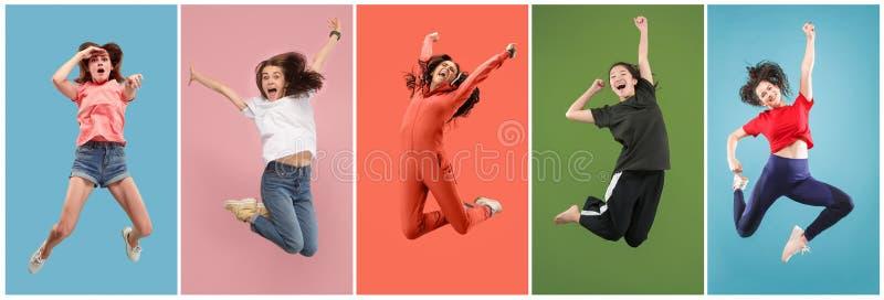 在移动的自由 相当跳跃反对橙色背景的少妇 库存图片