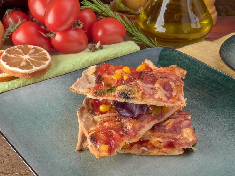 在稀薄的面团的比萨 切片蒜味咸腊肠和火腿、橄榄和蕃茄 免版税库存图片