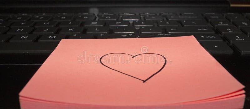 在稠粘的笔记画的爱心脏被键盘 库存图片