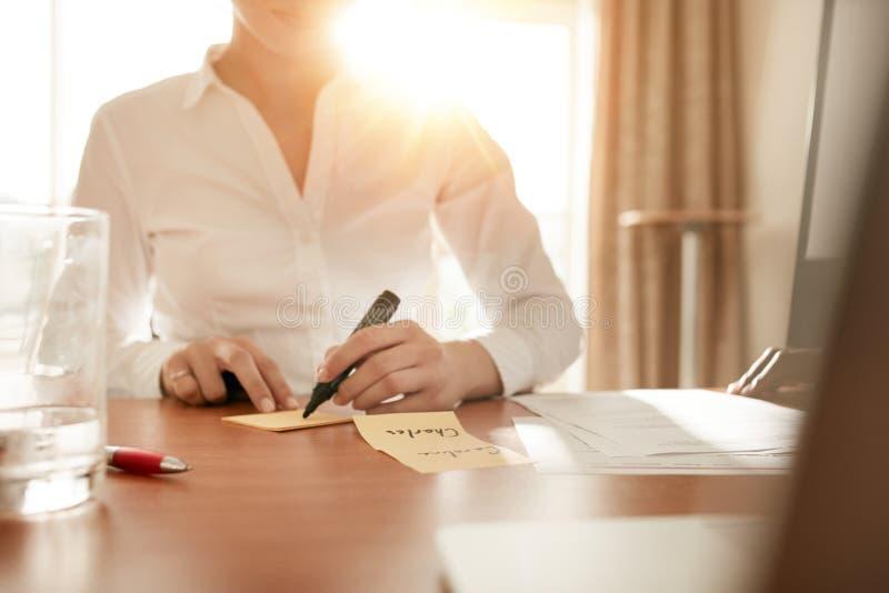 在稠粘的笔记的妇女文字在会议室 免版税库存照片