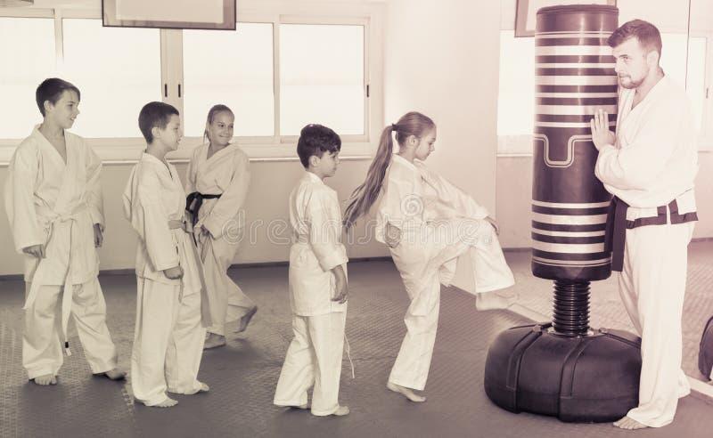 在空手道cla期间,训练空手道的孩子在沙袋踢 免版税库存图片
