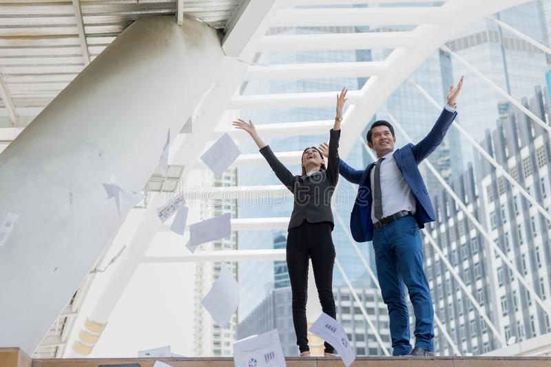 在空气和举两只手的亚洲商人和女实业家投掷的报纸对庆祝为成功在使命 免版税库存图片