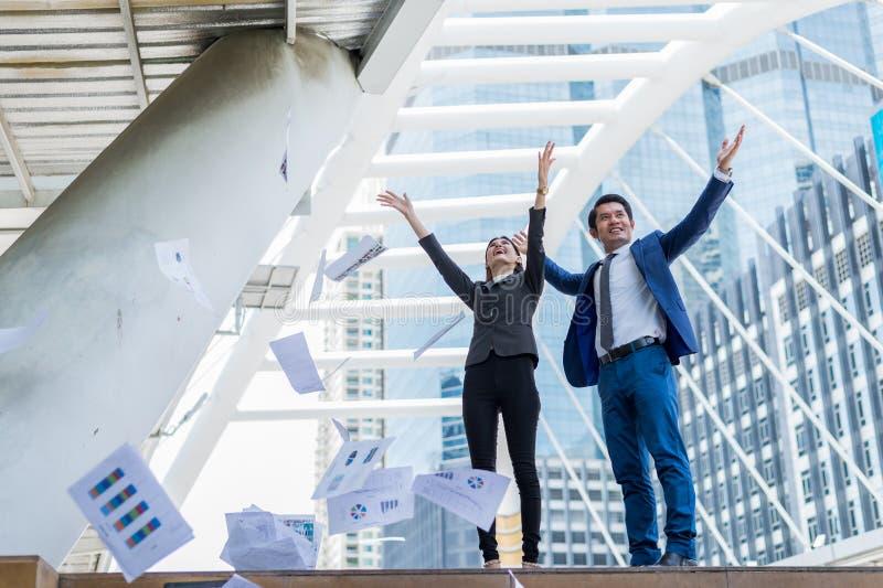 在空气和举两只手的亚洲商人和女实业家投掷的报纸对快乐和庆祝为成功 免版税库存照片